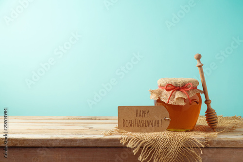 Jewish holiday Rosh Hashanah background with honey jar on wooden table