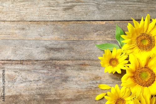 In de dag Zonnebloem Yellow sunflowers on wooden background, top view