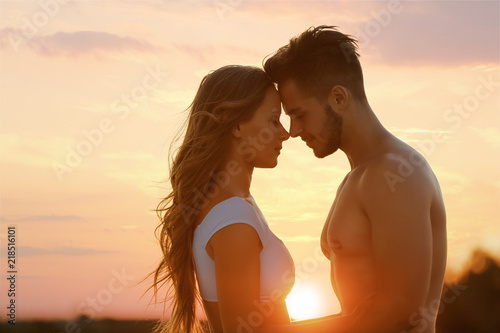 Happy young couple in beachwear outdoors at sunset