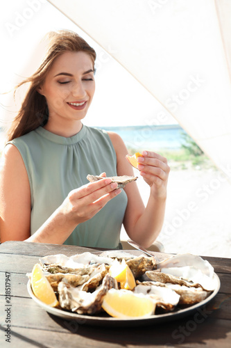 Woman eating fresh oyster at table, outdoors