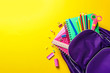 canvas print picture - Flat lay composition with backpack and school stationery on color background