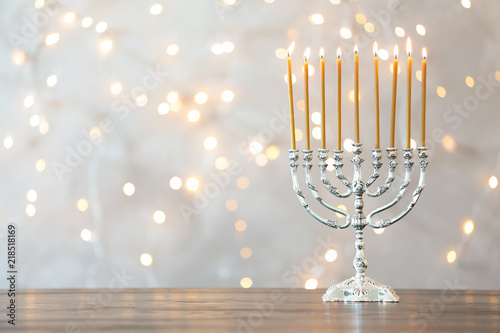 Fotografie, Obraz Hanukkah menorah with candles on table against blurred lights