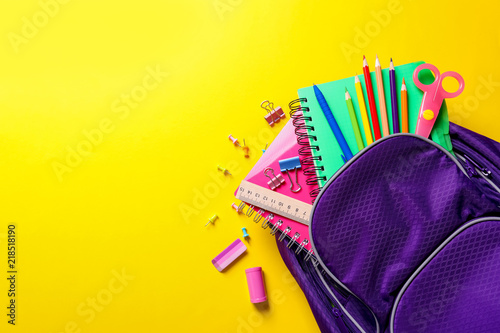 Fototapeta Flat lay composition with backpack and school stationery on color background obraz