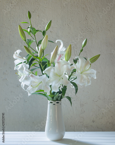 beautiful white lily in vase on background old wall