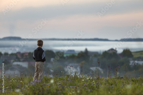 Poster Donkergrijs Back of young child boy alone on grassy hill top on foggy village among green trees background.