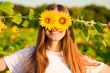 Happy Joyful Girl With Sunflower Enjoying Nature And Laughing On Summer Sunflower Field