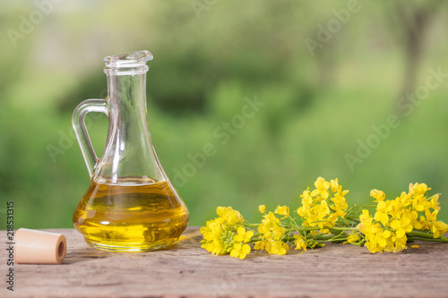 Foto op Plexiglas Kruiderij rapeseed oil (canola) and rape flowers on wooden table