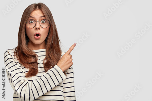 Fotografija  Horizontal shot of beautiful young Caucasian female with surprised expression, p