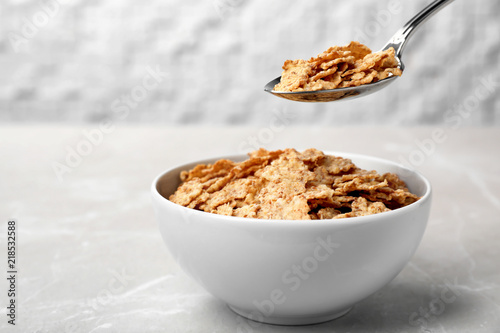 Spoon with cornflakes over bowl on table. Whole grain cereal Fototapeta