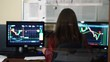 Woman on the background of monitors full of diagrams. Financial trader female checking stock market data in office. Working process of company. Shot in 4K (UHD).
