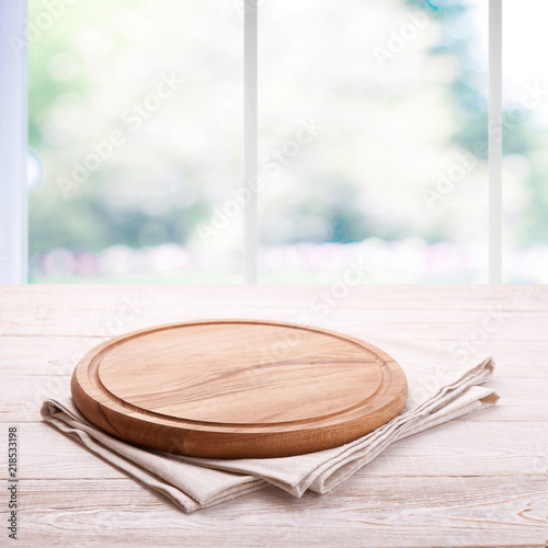 Board for pizza and tablecloth on empty wooden table near the window in kitchen. Canvas, dish towels on white background top view mock up. Selective focus.