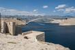 Croazia: vista panoramica delle rovine di una torre di guardia e del Paški Most, il ponte del 1968 che collega la Croazia con l'isola di Pago, la quinta isola più grande della costa croata