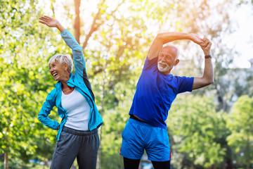 Happy fit senior couple exercising in park.