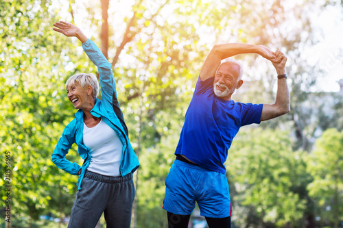 Fotografía  Happy fit senior couple exercising in park.