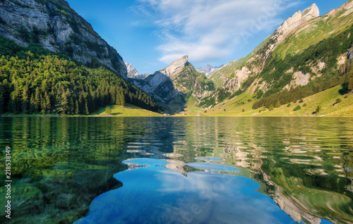 Mountains and lake in the Switzerland. Reflection on the water surface. Natural landscape in the Switzerland at the summer time. Lake and wave