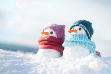 Two Little Snowmen The Girl And The Boy In Knitted Caps And Scarfs On Snow In The Winter. Christmas Card With A Lovely Snowman, Copy Space