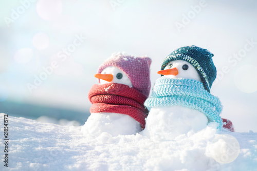 Fotografie, Obraz  Two little snowmen the girl and the boy in knitted caps and scarfs on snow in the winter