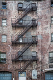 Worn brick building with metal fire escape - 218545960