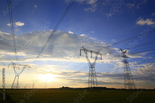 Foto  High voltage tower in the field, in the setting of the sunset