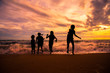 Silhouette children group enjoy playing sea waves on the beach in sunset with beautiful twilight sky