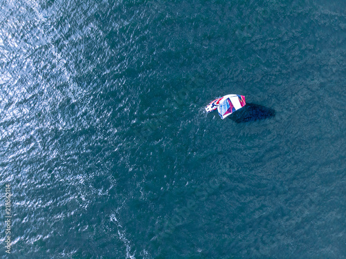 aerial view of a surfer on water during summer day. drone photography