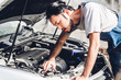 Professional car mechanic in uniform fixing a car engine and repairing checking under the car hood in auto service