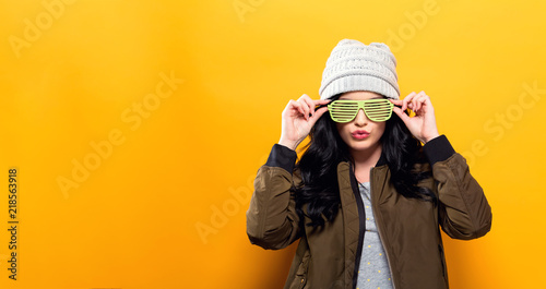 Photo Fashionable woman with attitude in bomber jacket on a golden yellow background