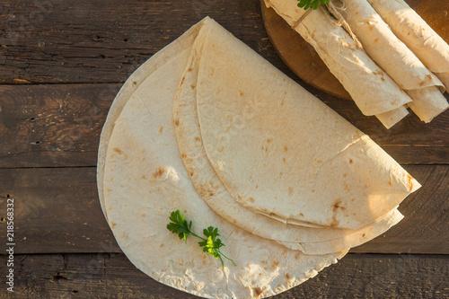 Armenian flat bread lavash. Pita bread on black cwood background. Copy space.