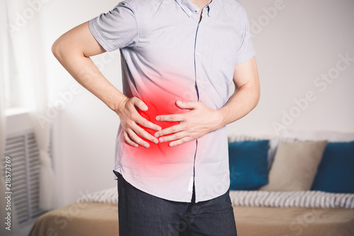 Photo Attack of appendicitis, man with abdominal pain suffering at home