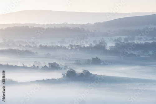 Poster de jardin Taupe Stunning foggy English rural landscape at sunrise in Winter with layers rolling through the fields