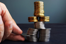Financial Stability Concept. Man Holding Coin In The Coins Stack.