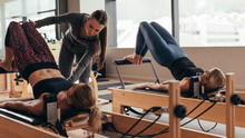 Female Pilates Trainer Helping A Pilates Woman During Training