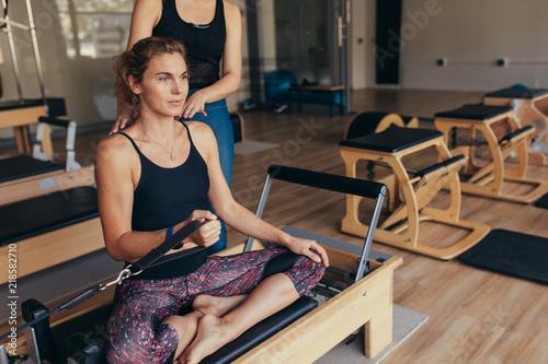 Fototapeta Woman pulling a stretch band  sitting on pilates training machin