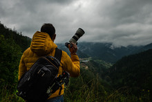 A Man In A Vibrant Yellow Coat And With A Backpack Is Holding A Camera With Large Lens With The Misty Mountains And Valley In The Background On A Rainy Cloudy Day.