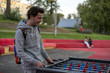 dissatisfied young man playing tablefootball in park in moscow