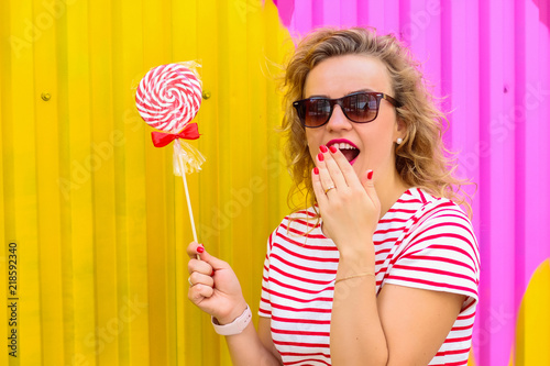 Portrait of a young beautiful bright girl with a colorful lollipop on a yellow-p Canvas Print