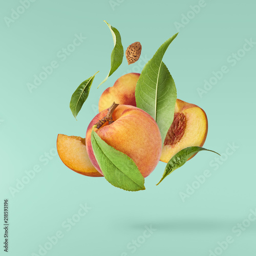 Flying fresh ripe peach with green leaves isolated Wall mural