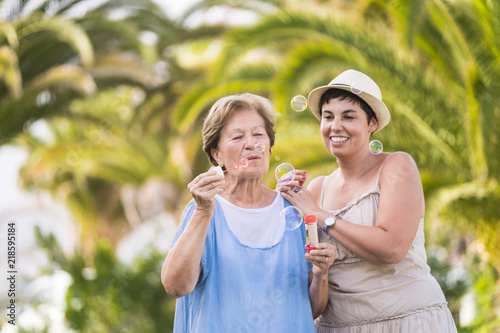 Fotografie, Obraz  mother and doughter caucasian couple play together blowing bubble soap in outdoor leisure activity