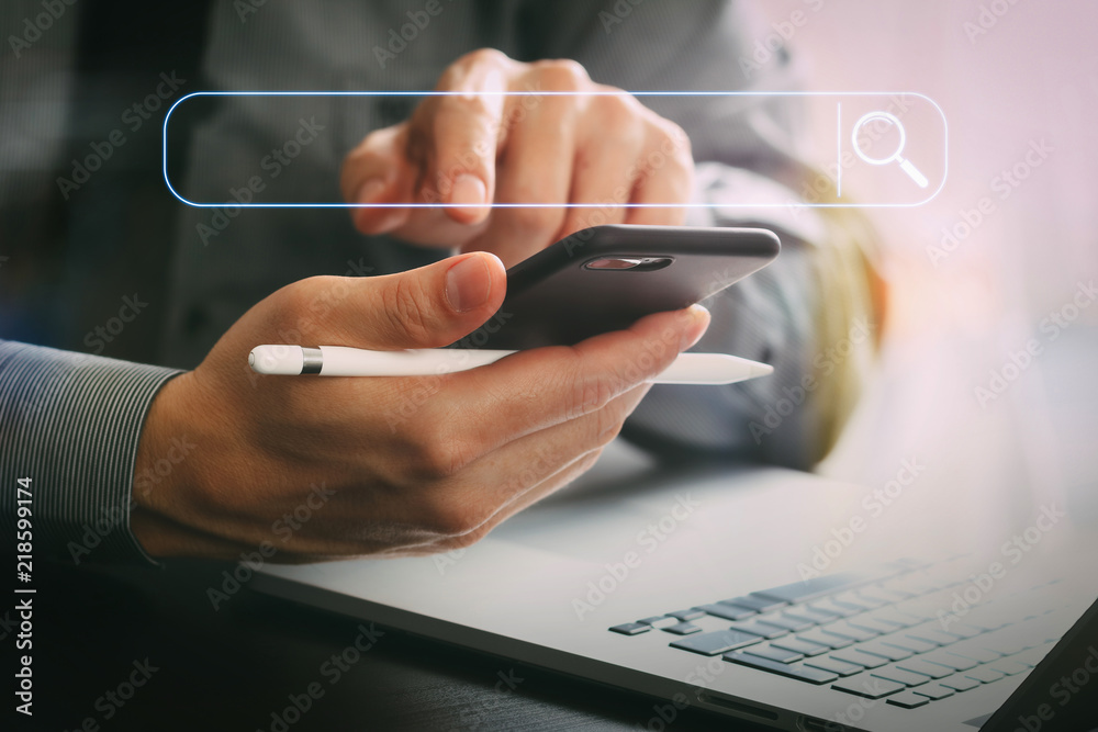 Fototapeta close up of businessman working with mobile phone and stylus pen and laptop computer on wooden desk in modern office