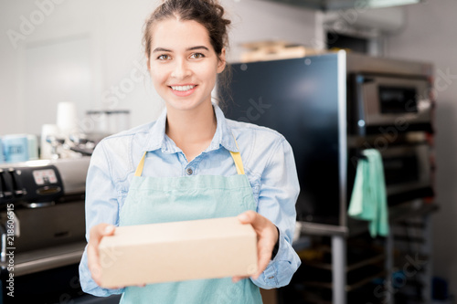 Waist up  portrait of smiling young  woman wearing apron holding box with takeaway food and looking at camera, copy space