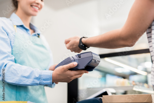 Low angle close up of unrecognizable woman paying via smart watch in local bakery, copy space