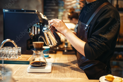 Photo Male barista pours boiling water into the glass