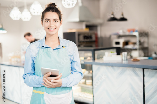 Waist up portrait of young waitress wearing apron holding note book posing looking at camera in cake shop or cafe and smiling, copy space