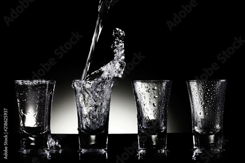 Fotografia  Water pouring into shot glasses