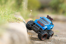 A Scene Of Blue RC Off-road Truck Car (Radio-controlled) On The Cement Floor Ground. (This Toy Has Some Dust From Children Playing)