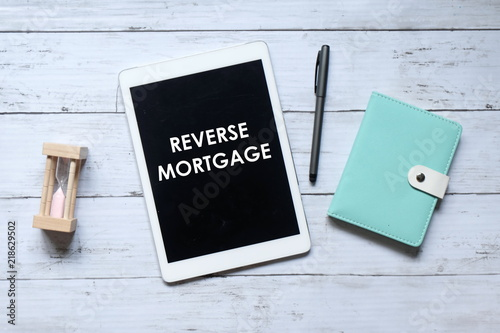 Fotografía  Top view of hourglass,notebook,pen and tablet pc written with REVERSE MORTGAGE on wooden background