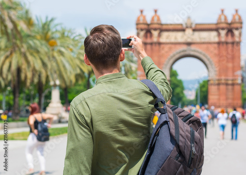 A young guy, tourist, takes pictures with a smartphone near the Arc de Triomf in Barcelona, Spain Canvas Print