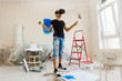 Young man with dark hair is painting the wall in white in his apartment. In his hands he holds a paint roller and paint brush. Can not decide what to choose.