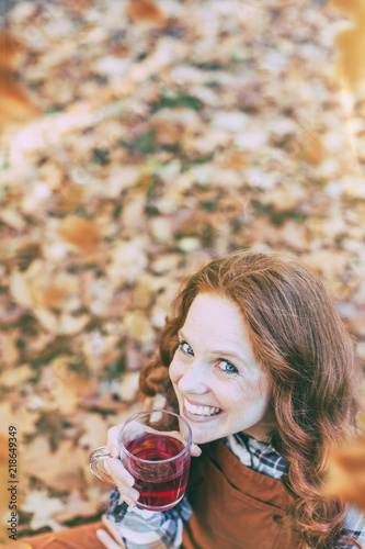 Valokuva  young beautiful redhead woman with tea