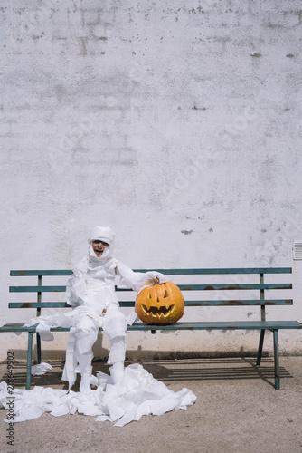 Fotografía  Little mummy boy with a pumpkin sitting in a street bench